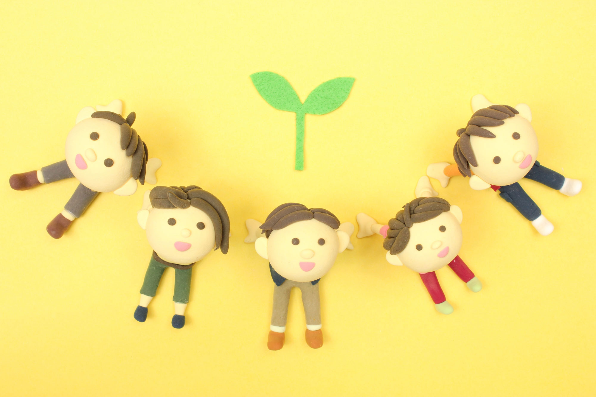 5つの人形が薄オレンジの背景で手をつなぐ画像
